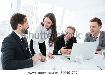 Business team talking by the table. Woman standing near the table. Men sitting