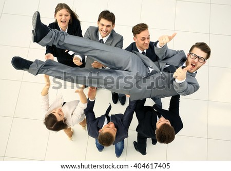 business team throwing his colleague. top view
