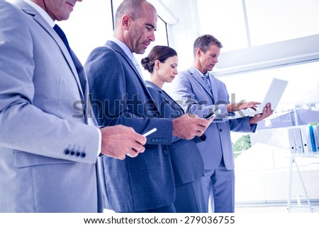 Business team using their media devices in the office - stock photo