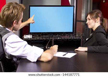 Business team watching a blank tv screen - stock photo
