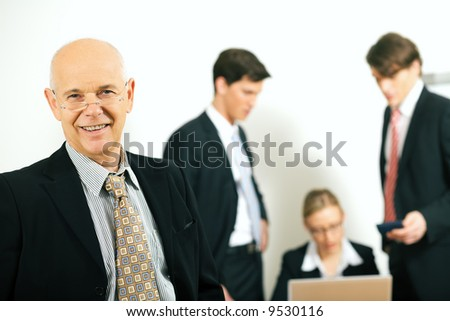 business team with a portrait of the team leader in foreground (selective focus only on the team leader!) - stock photo