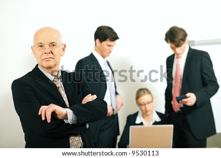 business team with a portrait of the very confident team leader in foreground (selective focus only on the team leader!) - stock photo