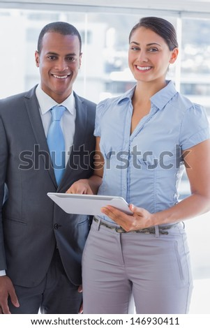 Business team with tablet pc smiling and looking at camera in office