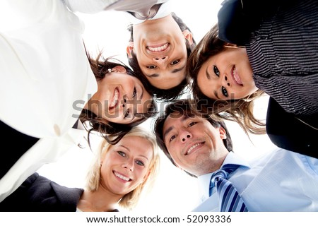 Business team with their heads together in the middle isolated over white - stock photo