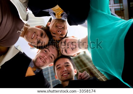 business team work in an office environment - businessmen and businesswomen with their heads together outside corporate buildings - stock photo