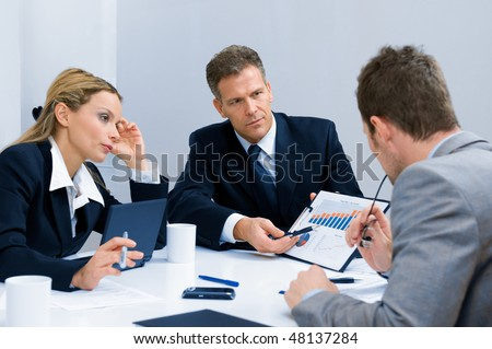 Business team working and discussing together their business plan at meeting in office - stock photo