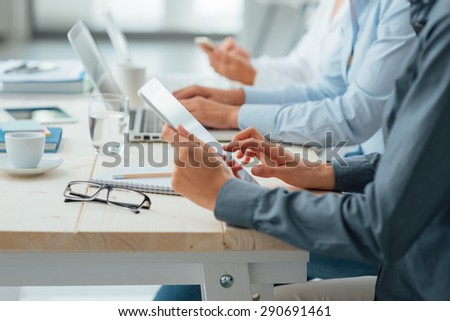 Business team working at office desk using a tablet, a laptop and a smart phone, hands close up, unrecognizable people - stock photo