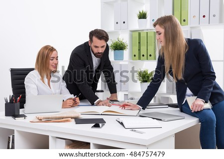 Business team working at project together. Woman sit on table and point at her notebook. Man and woman look at her notes and check her progress. Concept of teamwork
