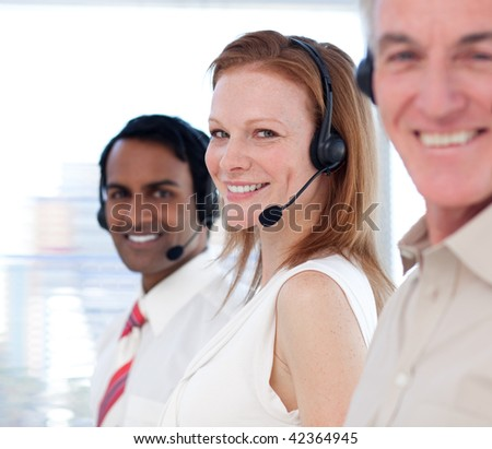 Business team working in a call center and smiling at the camera - stock photo