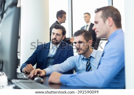 Business team working in corporate office. Businessmen trading stocks. Stock traders looking at graphs, indexes and numbers on multiple computer screens. Business success concept. - stock photo