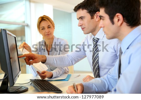 Business team working in front of desktop - stock photo