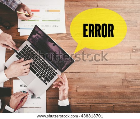 BUSINESS TEAM WORKING IN OFFICE WITH ERROR SPEECH BUBBLE ON DESK - stock photo