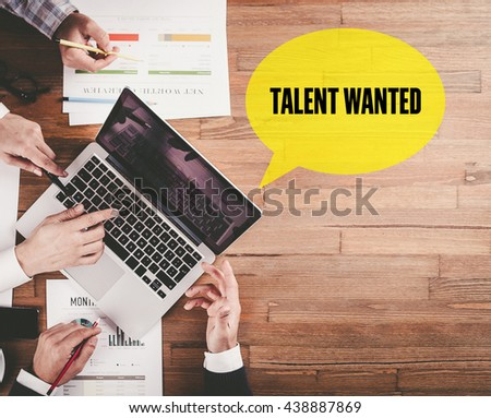 BUSINESS TEAM WORKING IN OFFICE WITH TALENT WANTED SPEECH BUBBLE ON DESK - stock photo