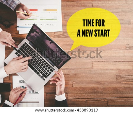 BUSINESS TEAM WORKING IN OFFICE WITH TIME FOR A NEW START SPEECH BUBBLE ON DESK - stock photo