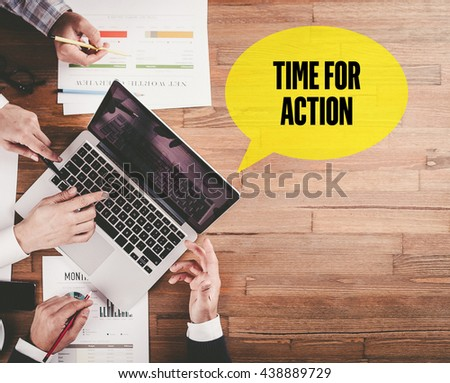 BUSINESS TEAM WORKING IN OFFICE WITH TIME FOR ACTION SPEECH BUBBLE ON DESK - stock photo