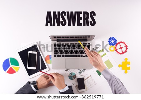 Business team working on desk with a single word ANSWERS - stock photo