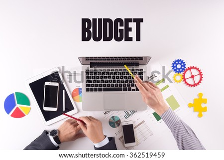 Business team working on desk with a single word BUDGET - stock photo