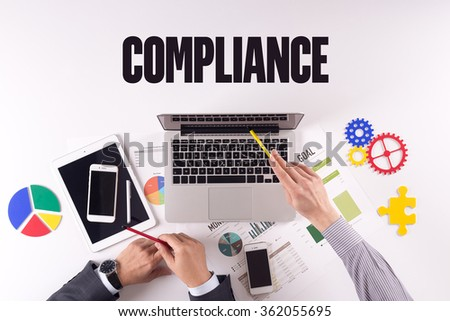 Business team working on desk with a single word COMPLIANCE - stock photo