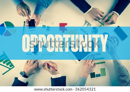 Business team working on desk with OPPORTUNITY word - stock photo