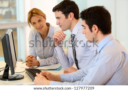 Business team working on front of desktop - stock photo
