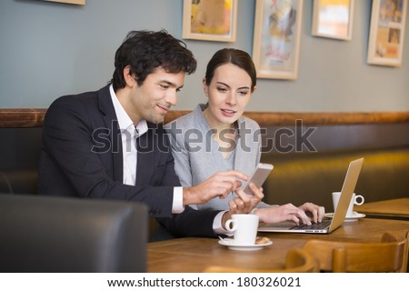 Business-team working on laptop at coffee bar, looking a mobile phone - stock photo
