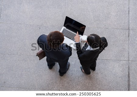 Business team working on laptop, view from the top - stock photo