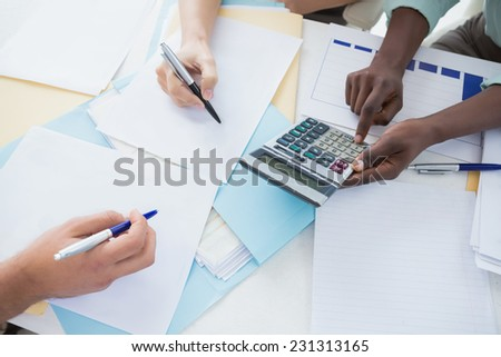 Business team working together at a meeting in creative office - stock photo
