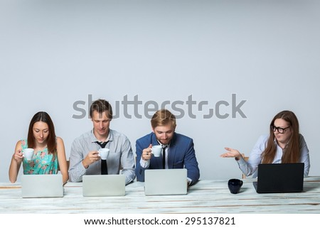 Business team working together at office on light gray background. boss is dissatisfied with the others drinking tea. copyspace image - stock photo