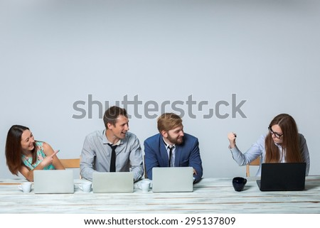 Business team working together at office on light gray background. headmistress threatening, others laughing. copyspace image - stock photo