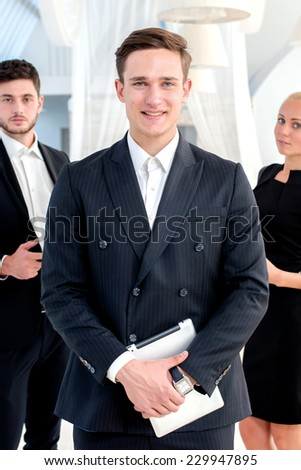 Business team. Young man in formal wear holding a the tablet and smiling at the camera while his colleagues are with laptop and mobile phone on the background - stock photo
