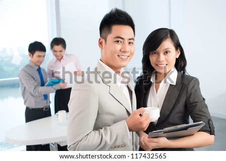 Business teams of two reviewing reports and analyzing financial data - stock photo