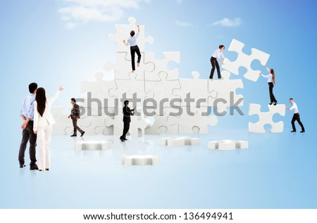 Business teamwork in action creating a puzzle on the cloud - stock photo