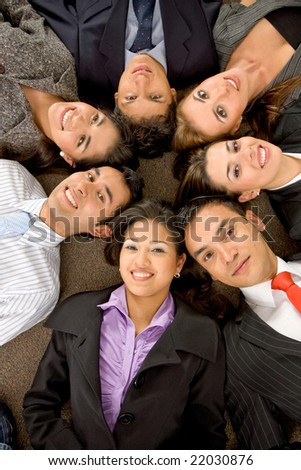business teamwork in an office with heads together on the floor
