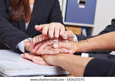 Business teamwork in the office with many hands stacked - stock photo