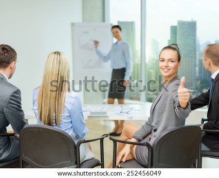 business, teamwork, people and success concept - happy businesswoman with team in office showing thumbs up - stock photo