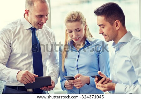 business, teamwork, people and technology concept - business team with tablet pc computer and smartphones meeting in office - stock photo