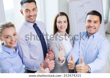 business, teamwork, success, people and gesture concept - smiling business team showing thumbs up in office - stock photo