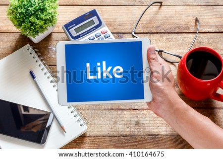 Business  technology and concept.Tablet with text inside Like on the table with offee. - stock photo