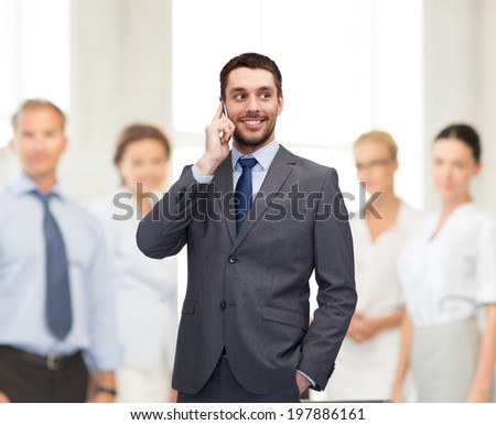 business, technology and education concept - friendly young smiling businessman with smartphone