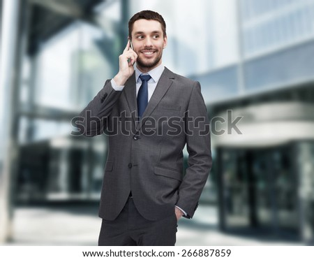 business, technology and education concept - friendly young smiling businessman with smartphone - stock photo