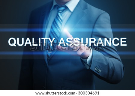 business, technology and internet concept - businessman pressing quality assurance button on virtual screens