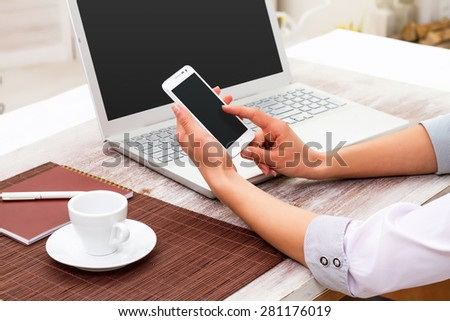 Business, technology and internet concept - Woman manager in the workplace works at the computer and smartphone - stock photo