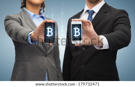 business, technology and internetconcept - businessman and businesswoman with bitcoin sign on smartphone screens - stock photo