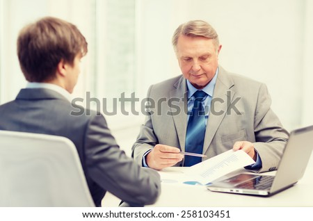 business, technology and office concept - older man and young man having meeting in office - stock photo