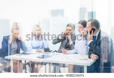 business, technology and office concept - serious business team with smartphones making calls in office - stock photo