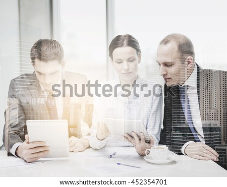 business, technology and office concept - serious business team with tablet pc computer, documents and coffee having discussion in office - stock photo