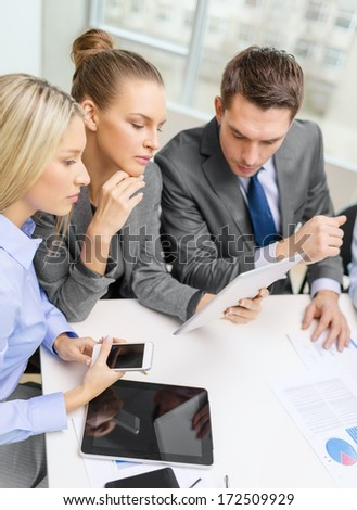 business, technology and office concept - serious business team with tablet pc, documents and smartphones having discussion in office