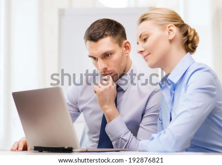 business, technology and office concept - serious businessman and businesswoman with laptop computer at office - stock photo
