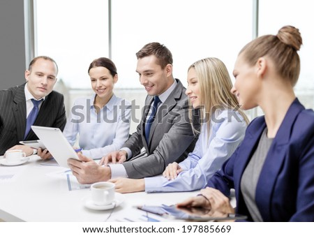 business, technology and office concept - smiling business team with tablet pc computer, documents and coffee having discussion in office - stock photo