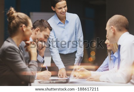 business, technology and office concept - smiling female boss talking to business team - stock photo